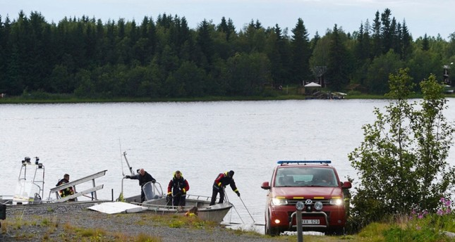Emergency services attend the accident site at a small harbor at Ume river, outside Umea, Sweden, Sunday July 14, 2019. (AP Photo)