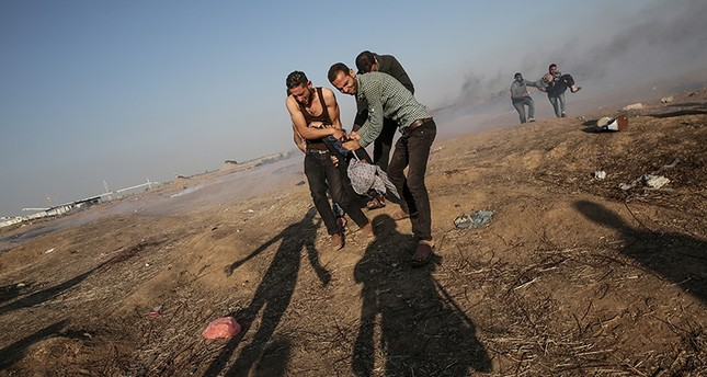 Palestinians protesters carry a wounded female protester during clashes near the border with Israel in the east of Gaza Strip, May 15, 2018. (EPA Photo)
