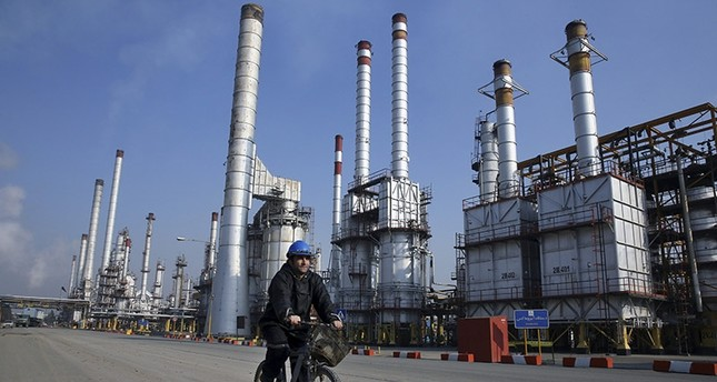 In this Dec. 22, 2014 file photo, an Iranian oil worker rides his bicycle at the Tehran oil refinery, south of the capital Tehran, Iran. (AP Photo)