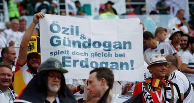 """German supporters at a game in the World Cup 2018 hold a sign saying """"Özil, Gündoğan go and play for Erdoğan."""""""