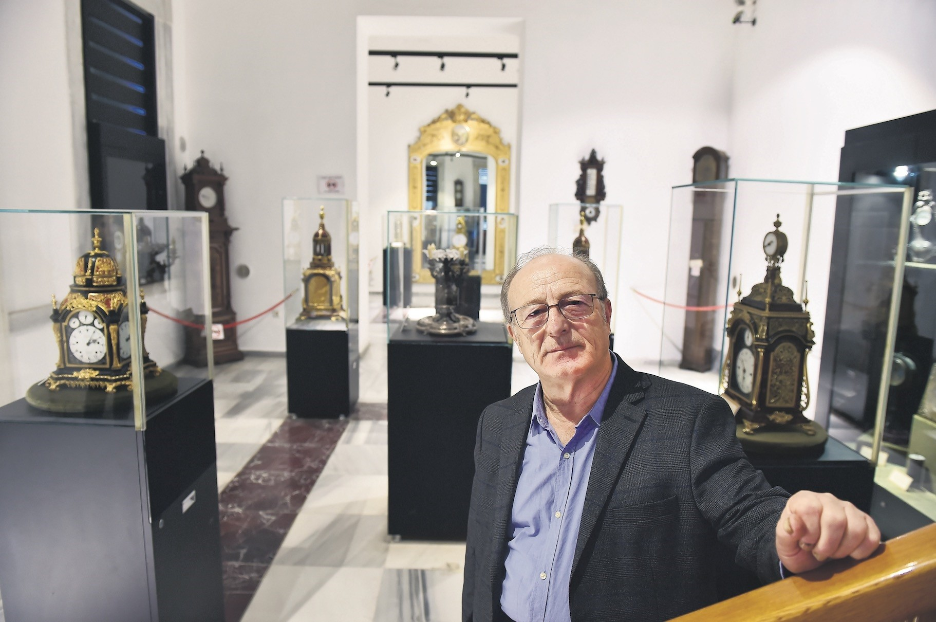 Recep Gu00fcrgen, who was trained by the clock master of Ottoman Sultan Abdu00fclhamidu2019s court, poses in the gallery where he displays antique clocks.