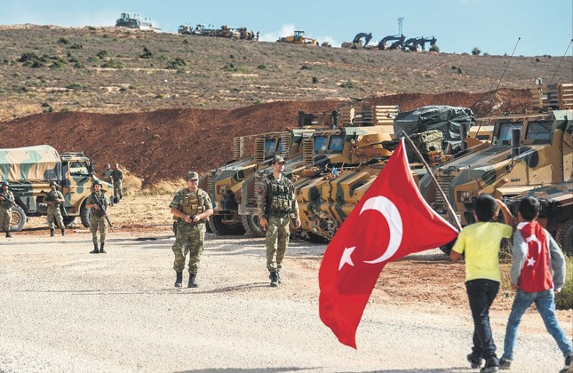 Turkish soldiers stand near armored vehicles as two young boys holding Turkish flags arrive during a demonstration in support of the Turkish army's Idlib offensive along the Turkey-Syria border near Reyhanlı, Hatay, Oct. 10, 2017.