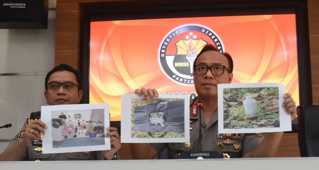 This picture taken on May 6, 2019 shows Indonesian police officers displaying photos of a suspected militant and evidence seized, during a press conference in Jakarta. AFP Photo