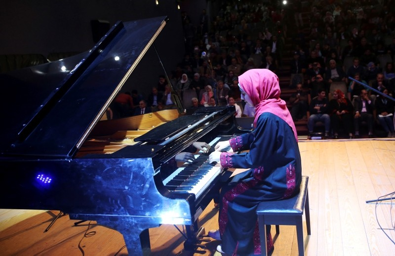 Palestinian pianist Yara Thabit plays the piano during a concert to mark the debut of Gaza's only grand piano after it was rescued from conflict, at a theater in Gaza City, Sunday, Nov. 25, 2018. (AP Photo)