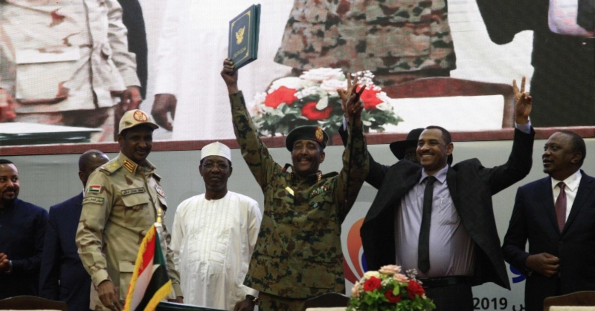 Sudan's protest leader Ahmad Rabie (2nd-R), flashes the victory gesture alongside General Abdel Fattah al-Burhan (C), the chief of Sudan's ruling Transitional Military Council (TMC) (AFP Photo)