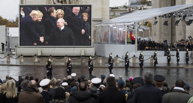 U.S. President Donald Trump (L) and Russian President Vladimir Putin (C) shown on a screen shaking hands during a ceremony for the Centenary of the World War I Armistice of Nov. 11, 1918, at the Arc de Triomphe, in Paris, France, Nov. 11.