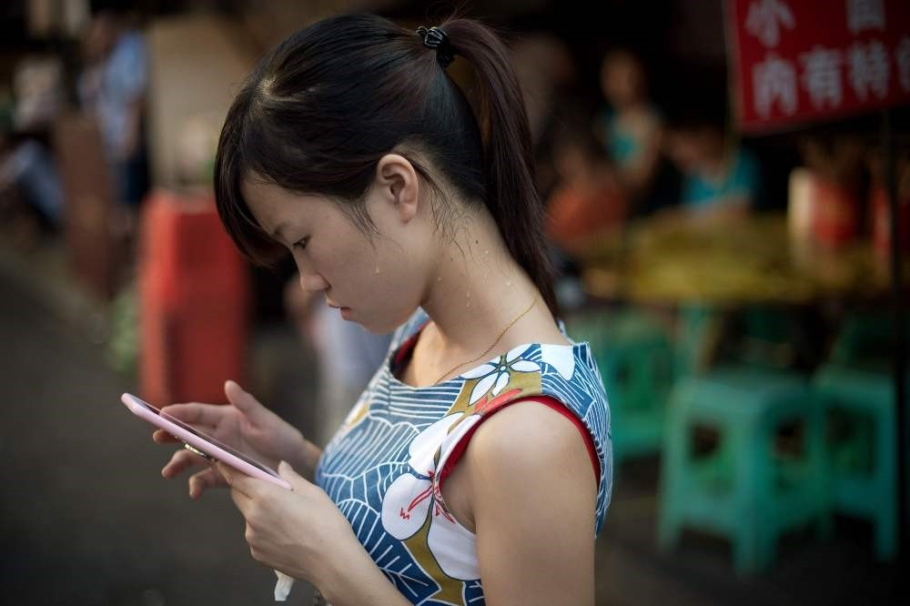 A young woman looks at her smartphone in Chongqing. (AFP Photo)