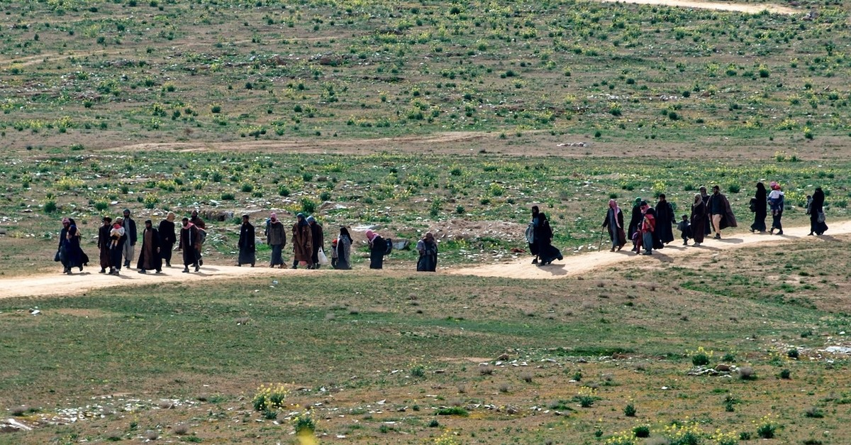Daesh terrorists and their families walk in a field as they leave the terrorist groupu2019s last territory, the village of Baghouz, Feb. 13, 2019.