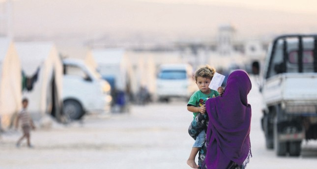 A displaced Syrian woman who took a shelter in camp Hope in Kafaldin on the Syrian-Turkish border holds a toddler, Sept. 13.