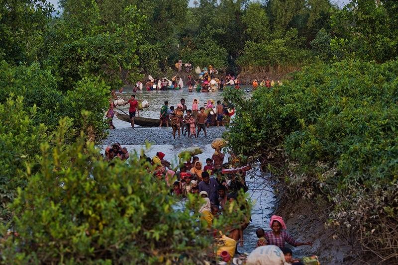 In this Nov. 1, 2017, file photo, groups of Rohingya Muslims cross the Naf river at the border between Myanmar and Bangladesh, near Palong Khali, Bangladesh. (AP Photo)
