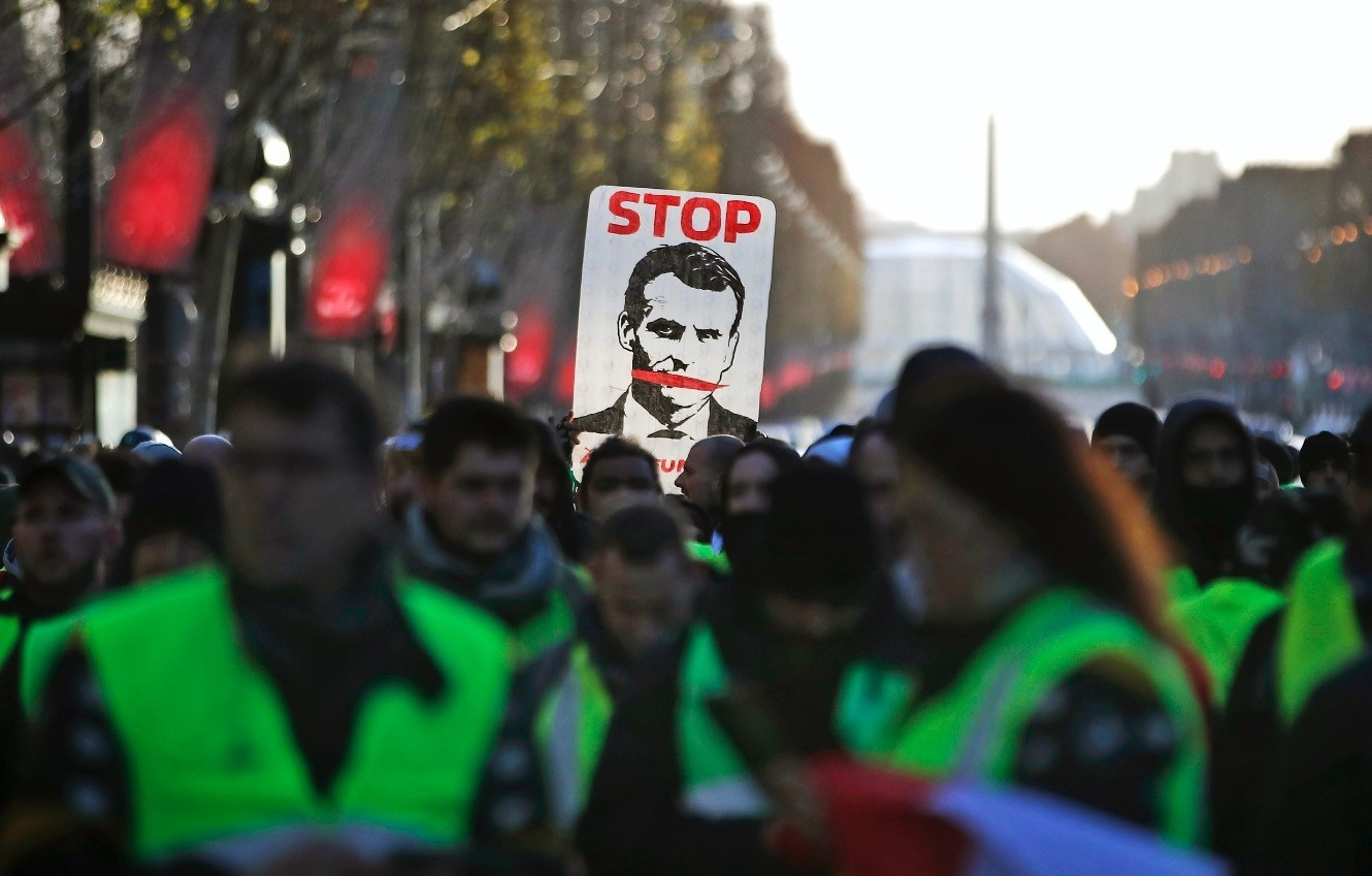 u2018Yellow vestu2019 protesters hold a sign showing u2018Stop Macronu2019 as they walk down the Champs Elysees Avenue to Place de la Concorde during a demonstration in Paris, Dec. 8.