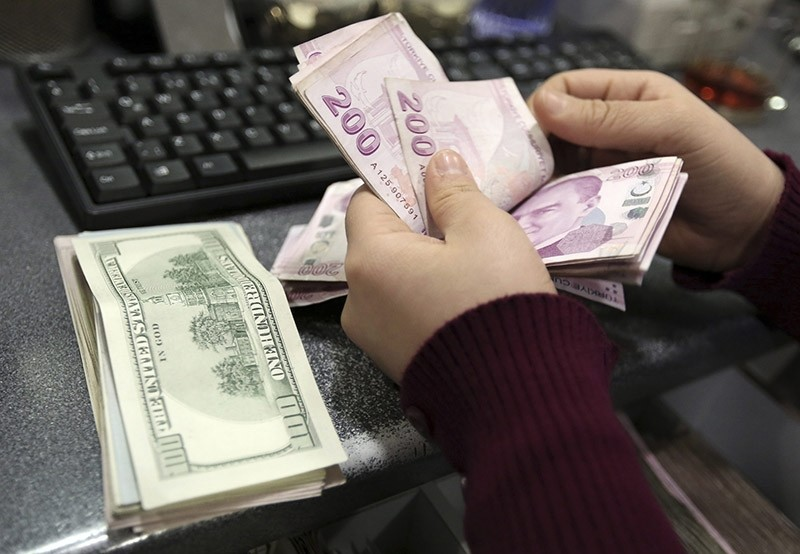 A woman counts U.S. dollar and Turkish lira banknotes at a currency exchange office in Istanbul. (File Photo)