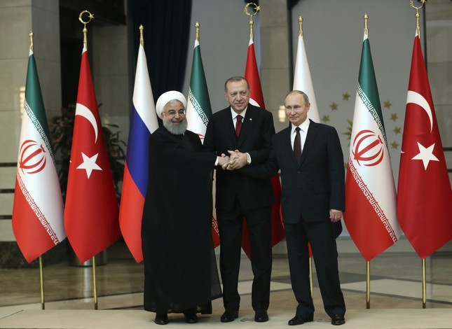 Iran's President Hassan Rouhani, (L), Russia's President Vladimir Putin, (R), and Turkey's President Recep Tayyip Erdoğan shake hands during a group photo in Ankara, April 8.