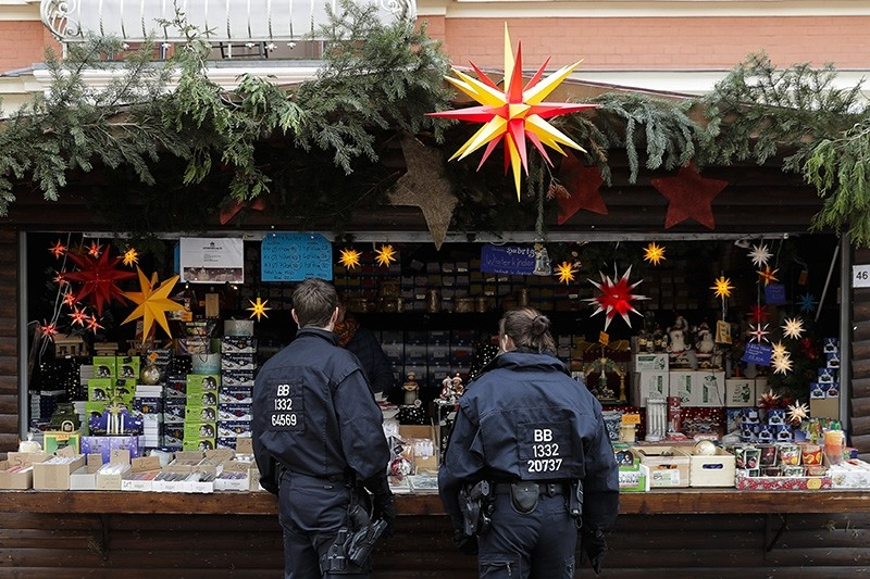 German police officers talk with a vendor on a Christmas market a day after a suspicious object was found in Potsdam, eastern Germany, Saturday, Dec. 2, 2017. (AP Photo)