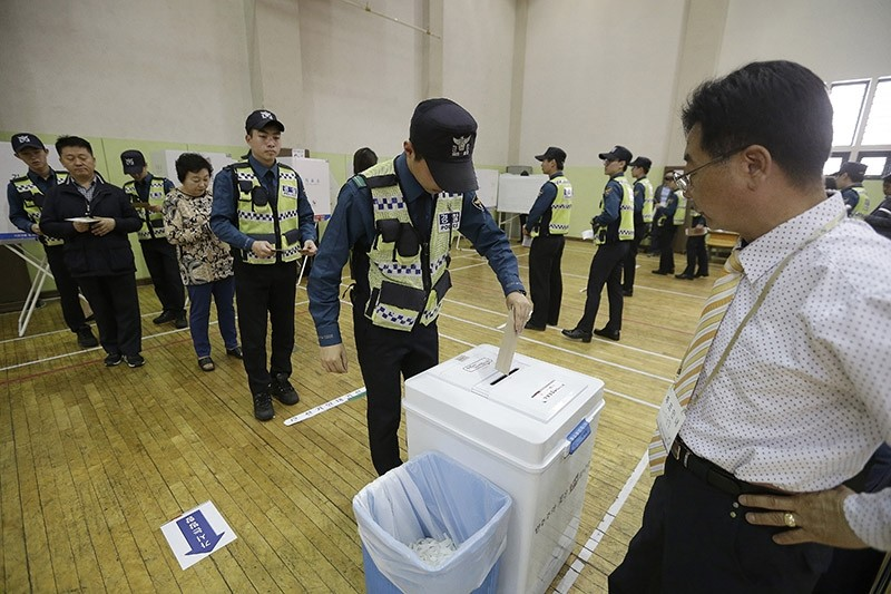 A South Korean police officer casts his preliminary vote for the upcoming May 9 presidential election at a local polling station in Seoul, South Korea (AP Photo)