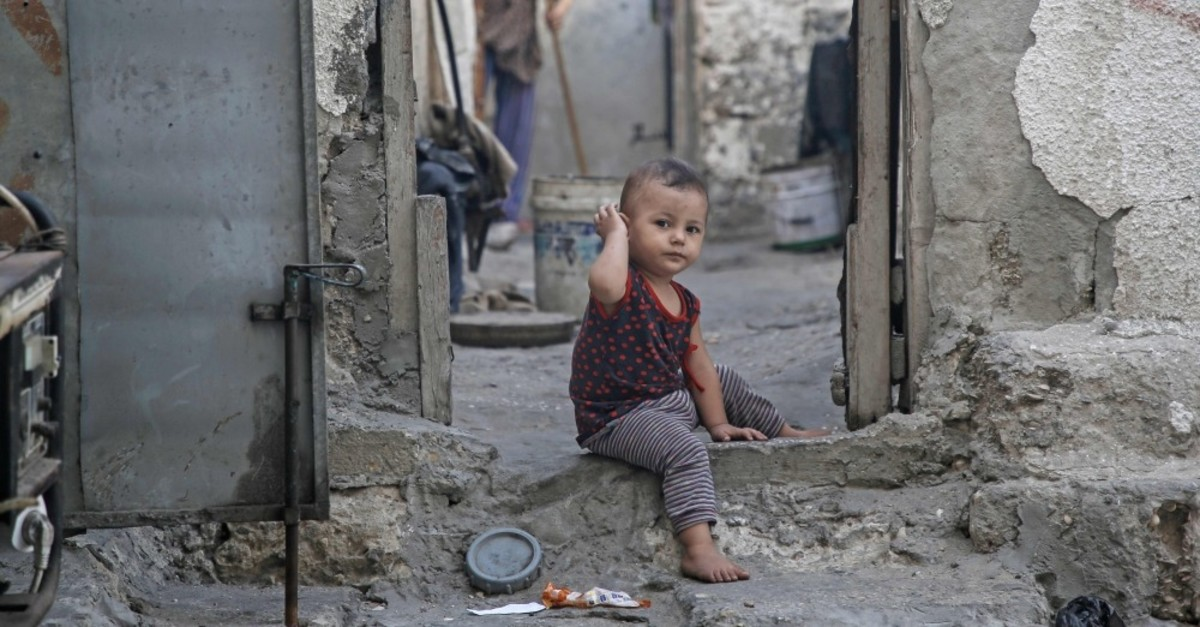 A toddler sits in the doorway of a deserted house as a woman sweeps in the background, Gaza City, Sept. 3, 2019.