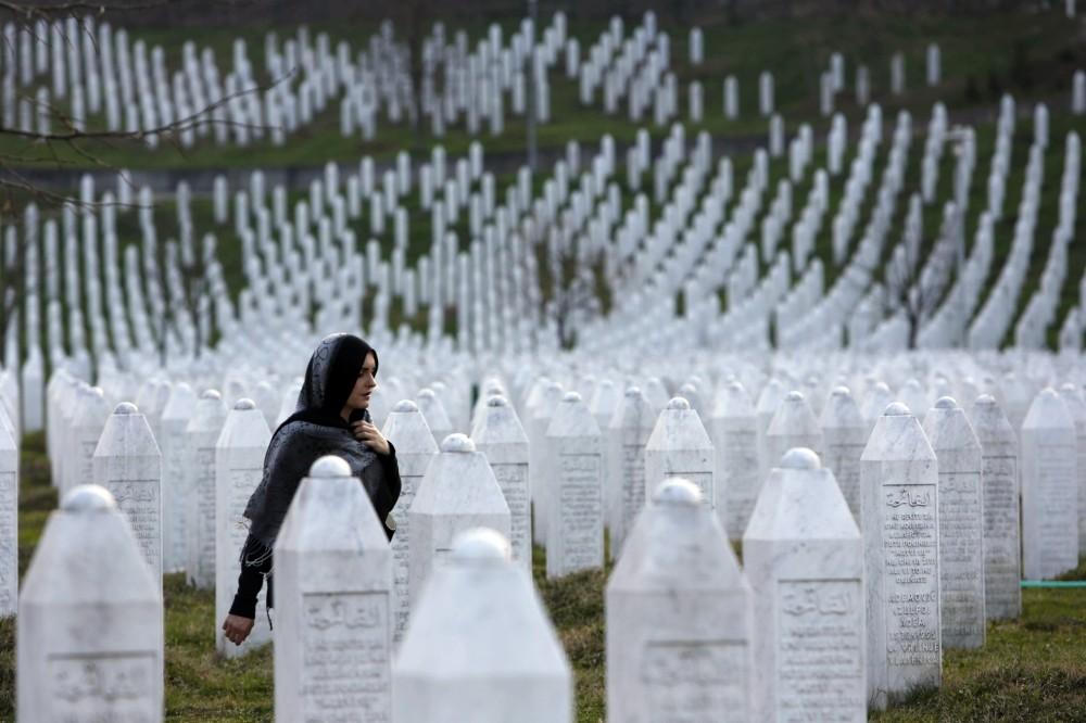 A Bosnian woman walks among gravestones at Memorial Centre Potocari near Srebrenica.