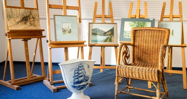 A picture taken on February 8, 2019 at the Weidler auction house in the southern German city of Nuremberg shows a wicker armchair, bearing a swastika, a vase and watercolours which are presumed to have belonged to Hitler (AFP Photo)
