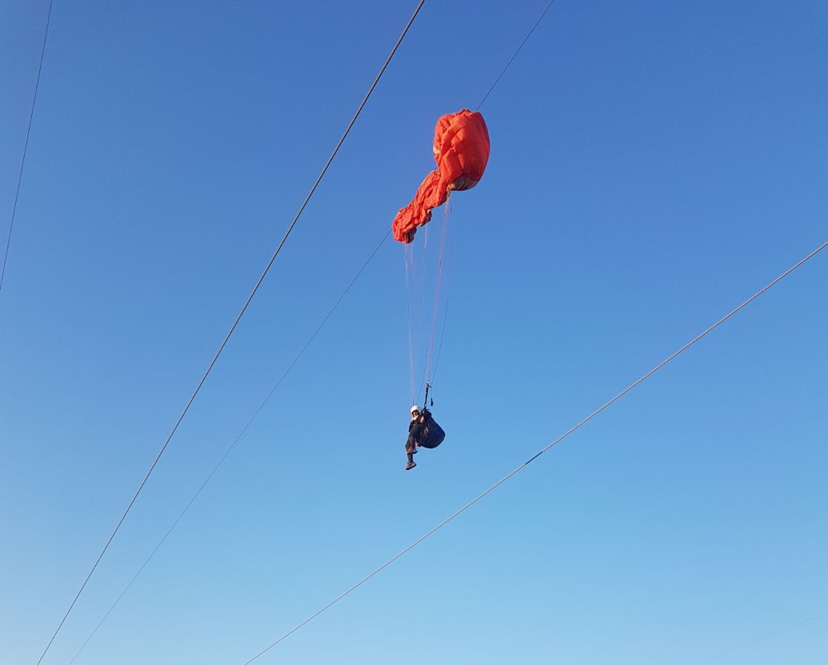 Nurcan Kaya was paragliding in Turkeyu2019s southern Kahramanmarau015f province when her parachute caught on a 154,000-volt power line, leaving her hanging for 2 hours. (DHA Photo)