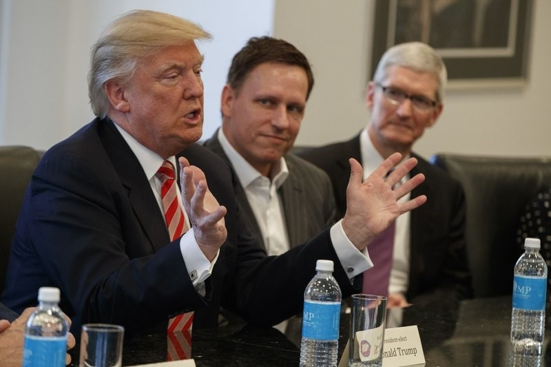 Apple CEO Tim Cook, right, and PayPal founder Peter Thiel, center, listen as then-President-elect Donald Trump speaks during a meeting with technology industry leaders at Trump Tower in New York, Wednesday, Dec. 14, 2016.