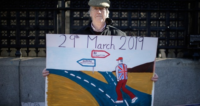 A leave the European Union supporter who didn't want to give his name poses for photographs outside the Houses of Parliament in London, Thursday, Feb. 14, 2019. (AP Photo)