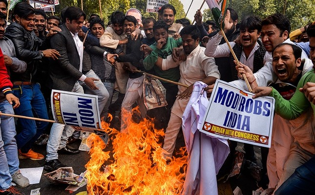 Indian supporters of the Congress Party shout slogans as they burn effigy of billionaire jeweller Nirav Modi in New Delhi on Feb. 16, 2018. AFP Photo