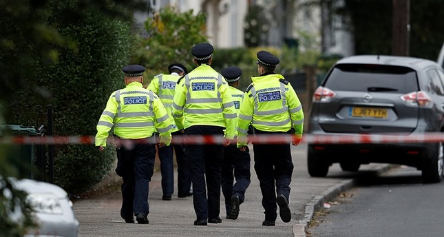 Police officers walk behind cordon tape set up around a property being searched after a man was arrested in connection with an explosion on a London Underground train (Reuters Photo)