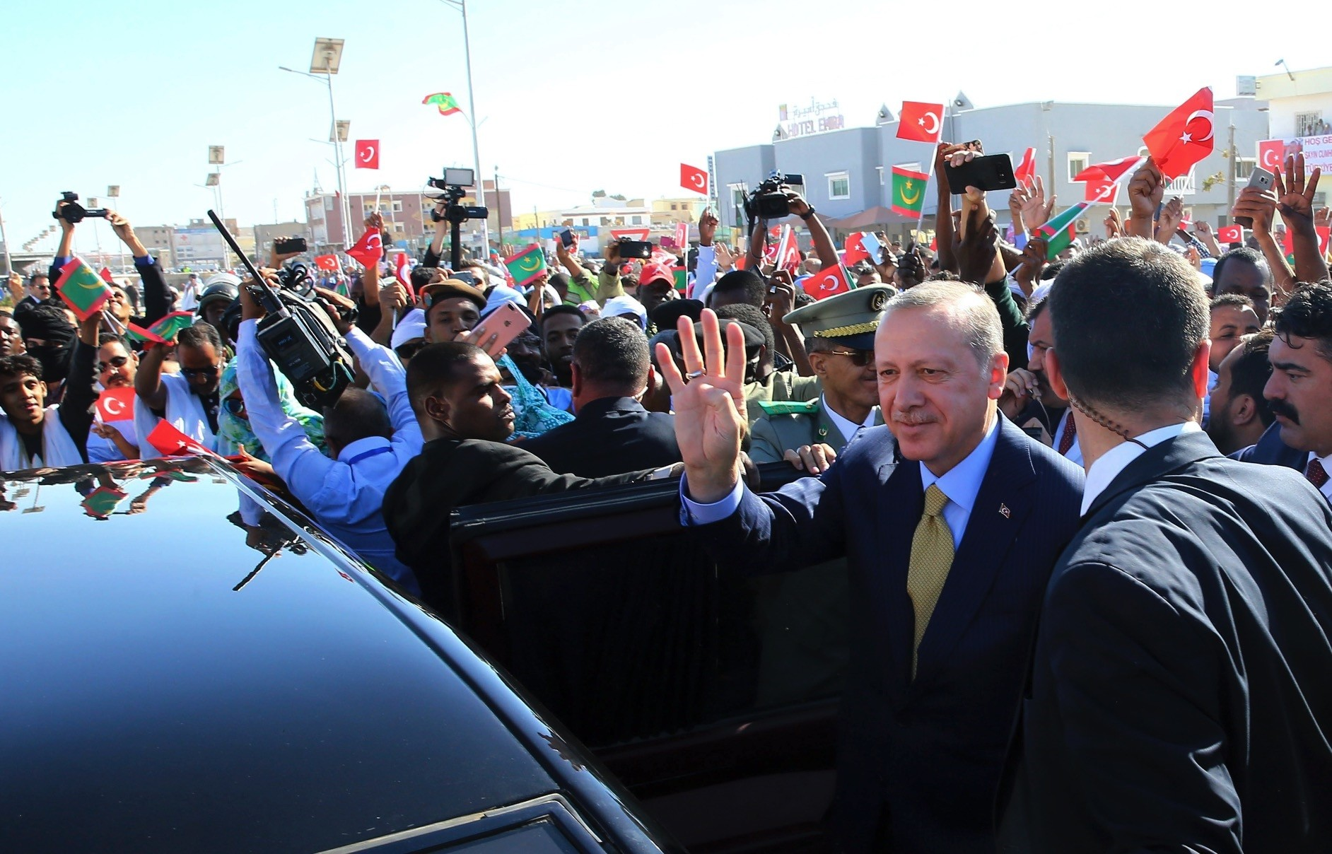 Turkish and Mauritanian security and people surround the car of President Erdou011fan as he waves during a welcoming ceremony at the airport in Nouakchott, Mauritania, Feb. 28.