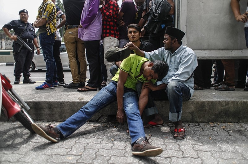 A Myanmar ethnic Rohingya Muslim (C, front) collapses as others line up after being arrested by the Malaysian police during a demonstration in Kuala Lumpur, Malaysia, 30 August 2017. (EPA Photo)