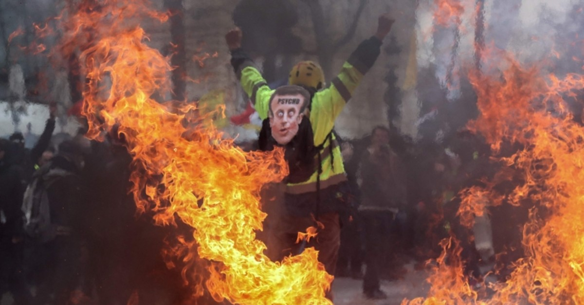 A Yellow Vest protester wearing a mask depicting the French President on which is written 'psycho', gestures behind flames rising from barricades, in Paris on March 16, 2019 (AFP Photo)