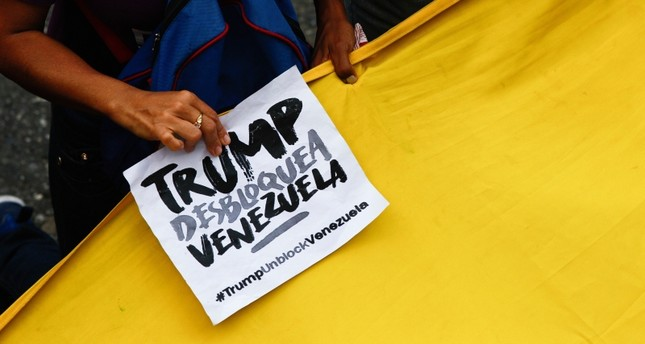 A government supporter holds a sign with a message that reads in Spanish: Trump unblock Venezuela during a protest against U.S. sanctions, in Caracas, Venezuela, Wednesday, Aug. 7, 2019. (AP Photo)