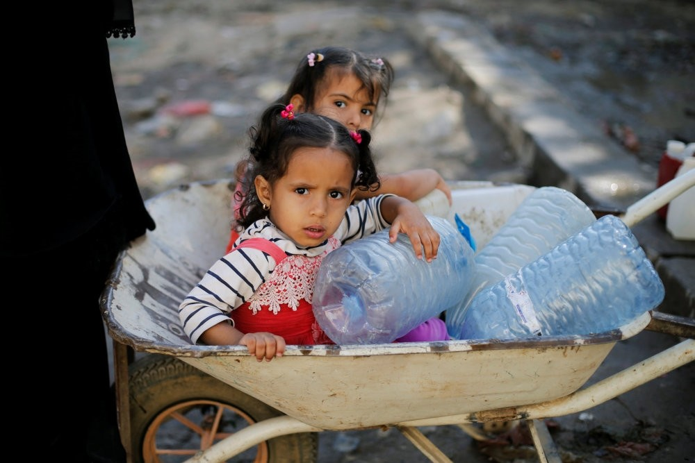 Girls wait to collect drinking water from a tap provided by a charity amid fears of a new cholera outbreak in Sanaa, Yemen Nov. 5.