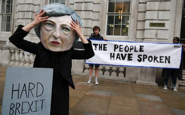 A demonstrator wears a mask depicting Britain's Prime Minister and leader of the Conservative Party Theresa May, and poses with a mock gravestone bearing the words Hard Brexit, RIP.
