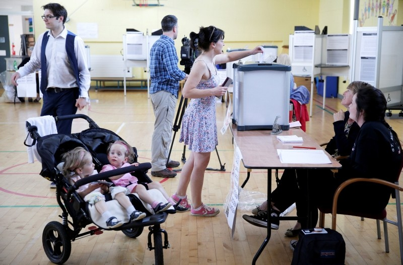 A woman votes while her children wait in their pushchair as Ireland holds a referendum on liberalizing its law on abortion, in Dublin, Ireland, May 25, 2018. (Reuters Photo)