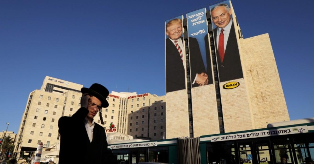 A man walks past a Likud election campaign billboard, depicting U.S. President Donald Trump shaking hands with Israeli Prime Minister Benjamin Netanyahu, in Jerusalem Feb. 4, 2019. (Reuters Photo)