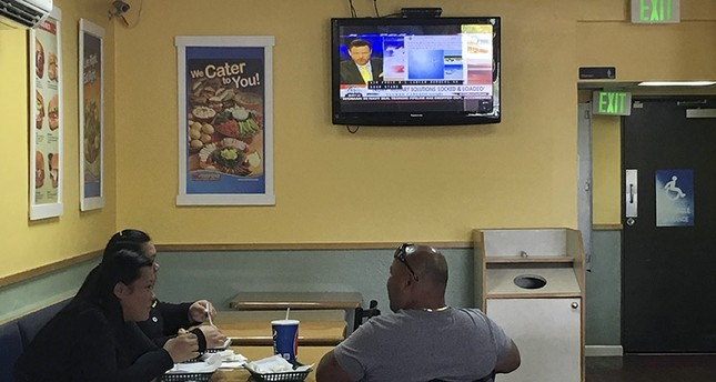 Residents watch TV news at a sandwich shop in Hagatna, Guam, Saturday, Aug. 12, 2017  (AP Photo)
