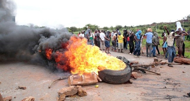 Protestors burn tires during a demonstration over the recent fuel price increase and the rising cost of living in the high-density suburb of Warren Park, Harare, Zimbabwe, Jan. 15, 2019. (EPA-EFE Photo)
