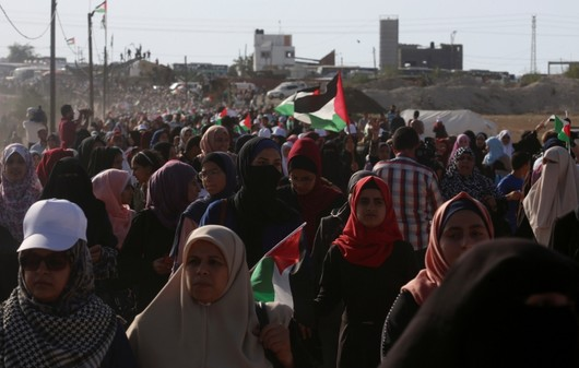 Palestinian women march while waving their national flags toward the Gaza Strip's border with Israel, during a protest east of Gaza City, July 3, 2018. (AP Photo)