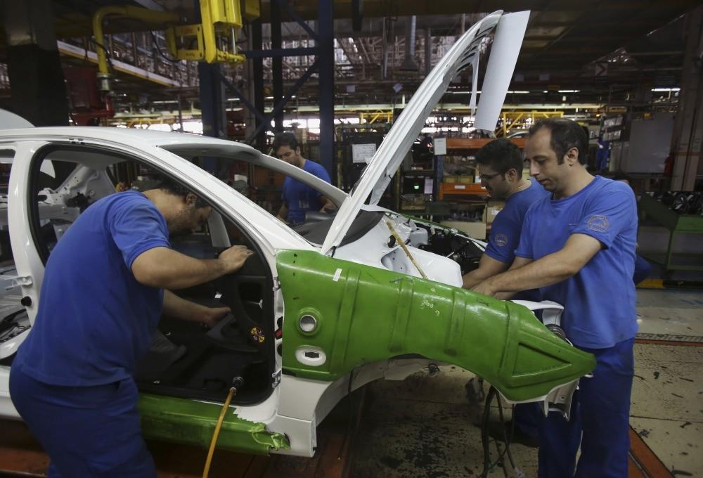 Iranian car workers assemble a car at the state-run Iran-Khodro automobile manufacturing plant near Tehran, Iran.