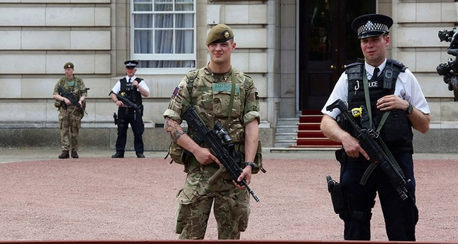 A member of the army joins police officers outside Buckingham Palace, London, May 24, 2017. AP Photo