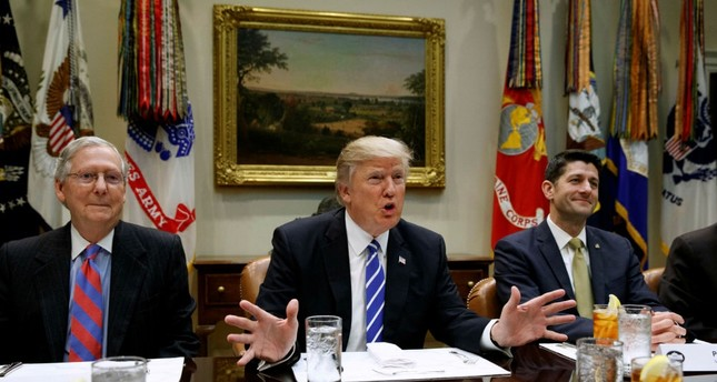 President Donald Trump (R), flanked by Senate Majority Leader Mitch McConnell in the Roosevelt Room of the White House in Washington, March 1