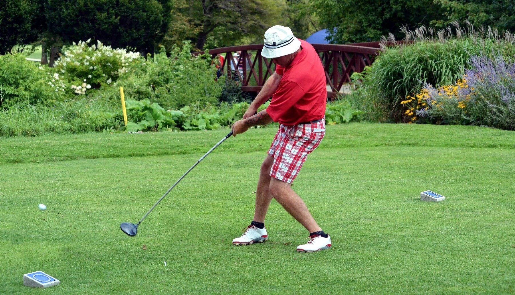 A left-handed golfer hits the ball during a tournament.