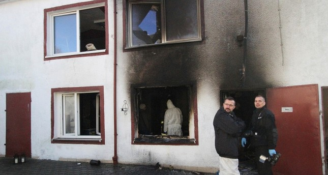 Forensic and other police experts examine the site of a fire in an Escape Room, in Koszalin, northern Poland, on Saturday, Jan. 5, 2019. (AP Photo)