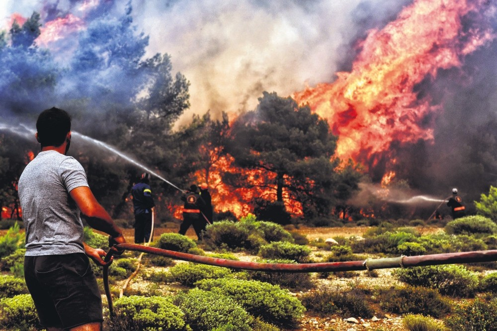 Firefighters and volunteers try to extinguish a wildfire raging in Verori, southern Greece, July 24.