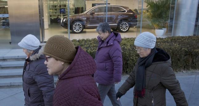 Elderly women enjoy their daily walk outside the Bentley Motors showroom in Beijing.