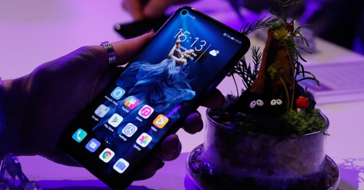 In this Tuesday, May 21, 2019 file photo, a member of the media tries out new Huawei Honor 20 series of phones following their global launch in London. (AP Photo)