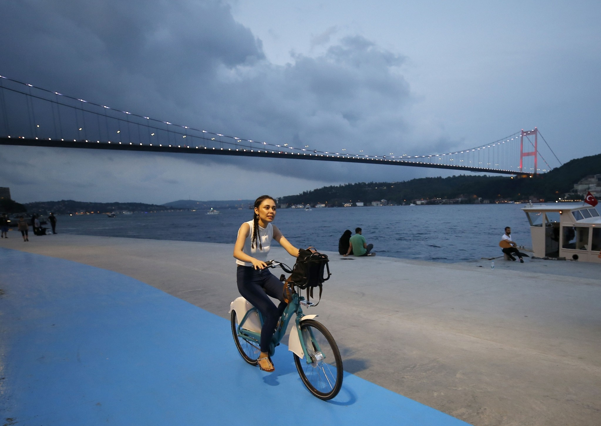 A woman rides near Istanbulu2019s water front with the bike she rented from u0130SBIKE.