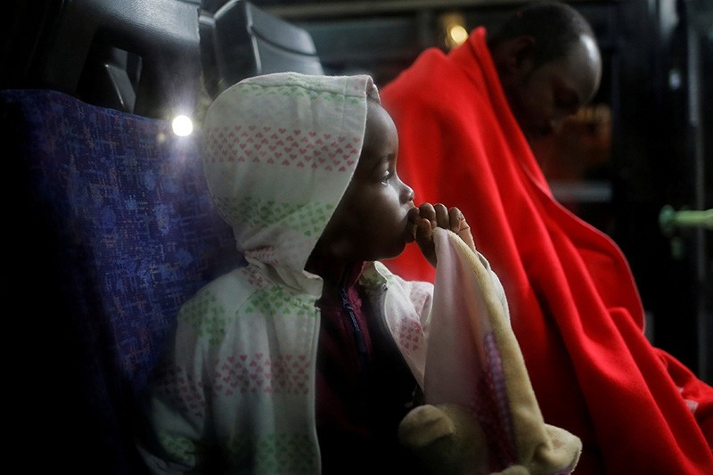 A 3-year-old migrant sits next to his father, following their arrival on a rescue boat after being intercepted off the coast in the Mediterranean Sea, as they sit in a bus at the port of Malaga, southern Spain, Nov. 11, 2018. (Reuters Photo)