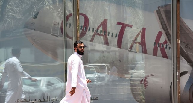 A picture taken Monday shows a man walking past a Qatar Airways branch in the Saudi capital Riyadh, after it had suspended all flights to Saudi Arabia following a severing of relations between major gulf states and gas-rich Qatar.