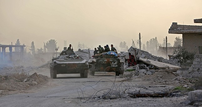 Syrian government forces drive military vehicles in al-Shifoniya as they advance in the opposition-held eastern Ghouta area on March 4, 2018. (AFP Photo)